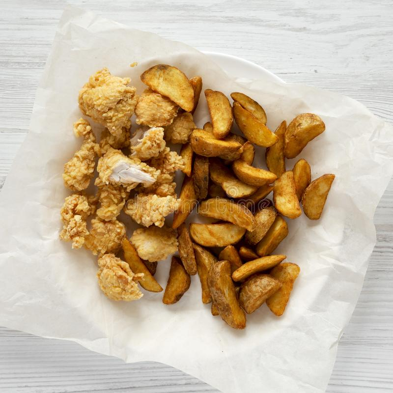 Fried potato wedges and chicken bites on a white wooden background, top view. Flat lay, overhead, from above. Fried potato wedges and chicken bites on a white royalty free stock photography