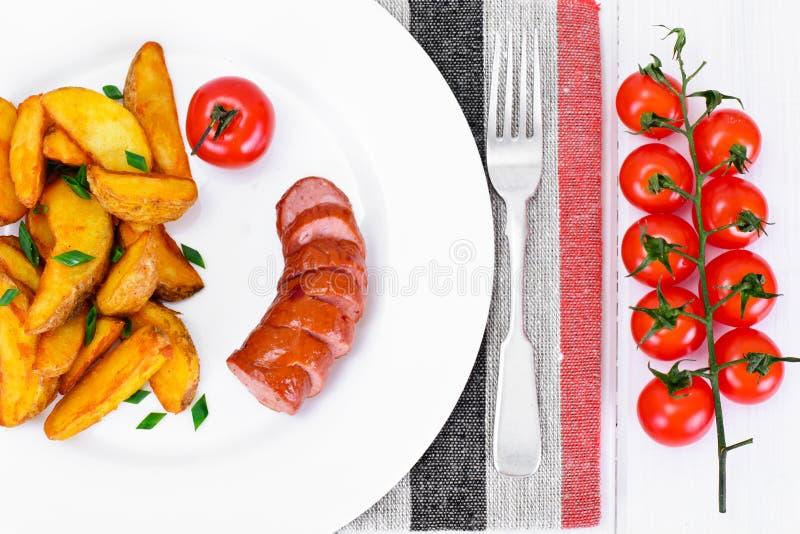 Fried Potato Wedges dans un rural et une saucisse image libre de droits