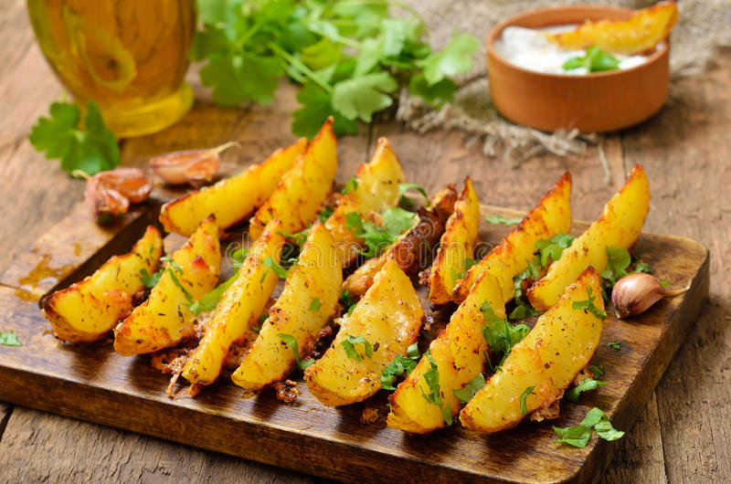 Fried potato wedges. With spices and herbs on cutting board royalty free stock photo