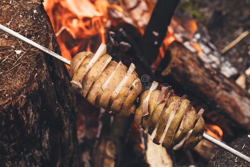 Fried potatoes with bacon on skewers. The concept of eating outdoors in the summer royalty free stock photography