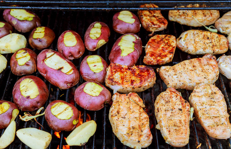 Fried potatoes with bacon on skewers. The concept of eating outdoors in the weekend. royalty free stock image