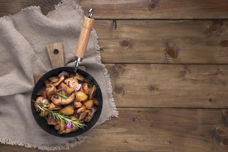 Fried potatoes in a black cast iron pan on a wooden background. Vintage photo and napkin in rustic style. Free space for text, top royalty free stock images