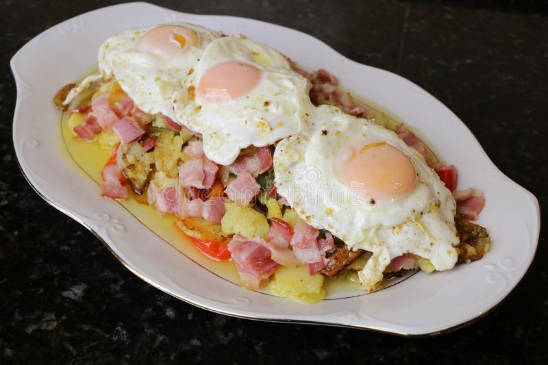 Fried potatoes with egg and bacon stock photos