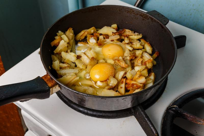 Fried potatoes with egg in a frying pan, Food bachelor. Cooked by a male royalty free stock photos