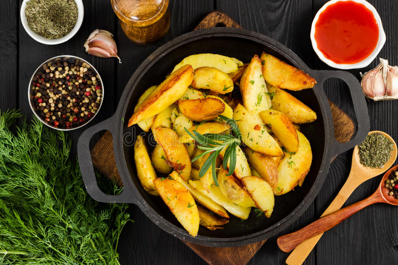 Fried potatoes with fresh rosemary in cast-iron pan. Top view. stock images