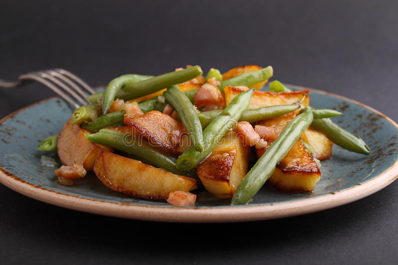 Fried potatoes with green beans. And bacon stock photo