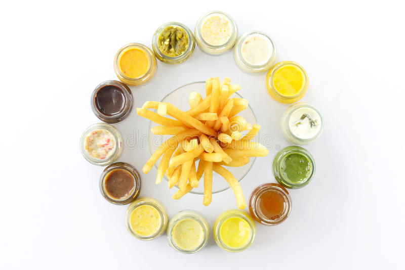 Top view french fries or fried potatoes with variety sauce dips in bottles on white floor. royalty free stock photography