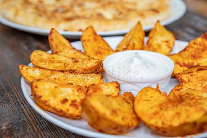 Fried potatoes with Mexican sauce on the plate stock photos