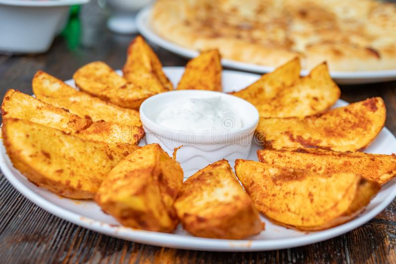 Fried potatoes with Mexican sauce on the plate stock images