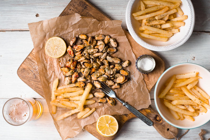 Fried potatoes, mussels, lemon on parchment and beer. Horizontal stock images