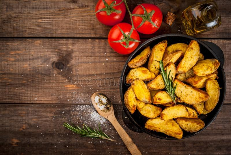 Fried potatoes in a rural style. With spices, rosemary and fresh tomatoes. On rustic pan, on a wooden table, top view copy space stock image