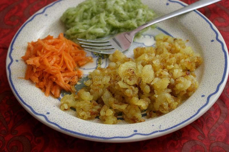 Fried potatoes with salad stock images