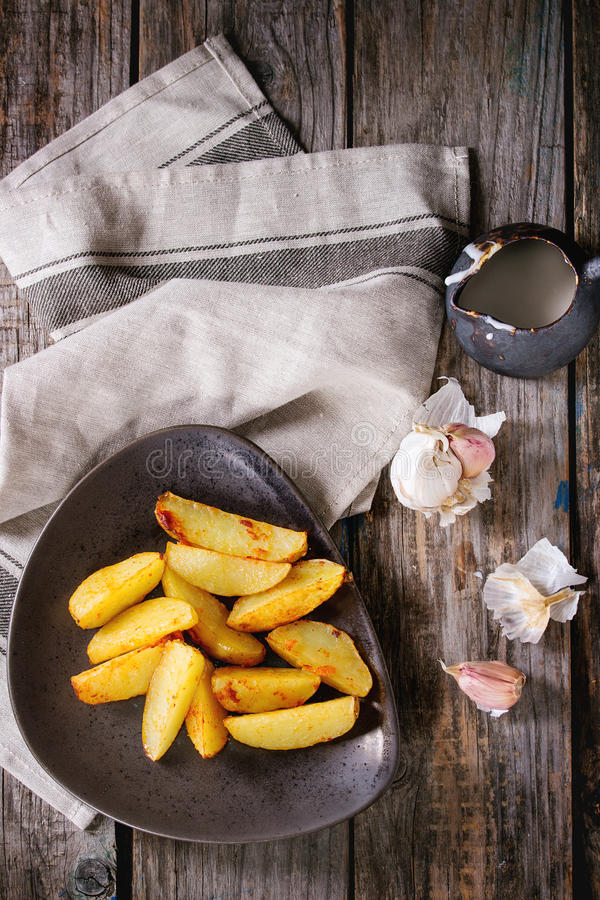 Fried potatoes with sauce. Fried country potatoes on brown ceramic plate, served with homemade aioli sauce in jug, garlic and vintage fork on gray linen napkin stock photos
