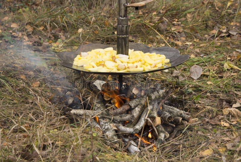 Fried Potatoes sur les pommes de terre de FireFried dans une casserole de fer accrochant au-dessus d'un feu photographie stock libre de droits