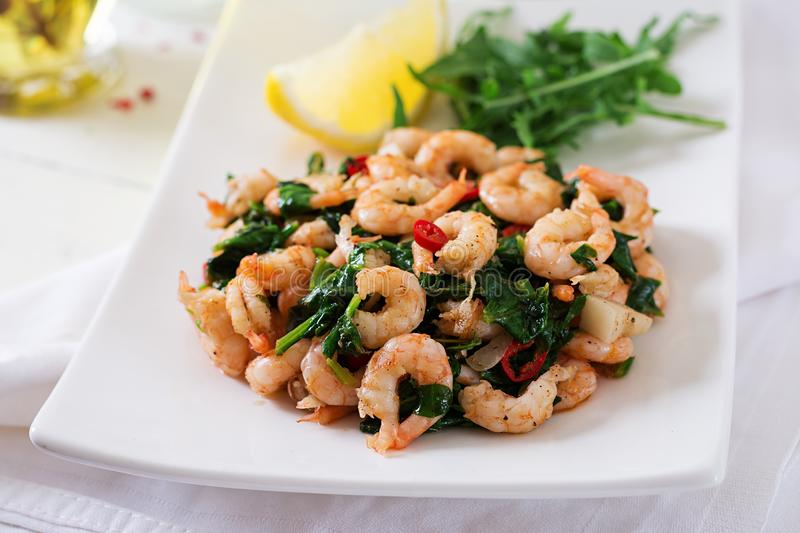 Fried prawns or shrimps with spinach, chili and garlic in white plate. Diet concept royalty free stock photography