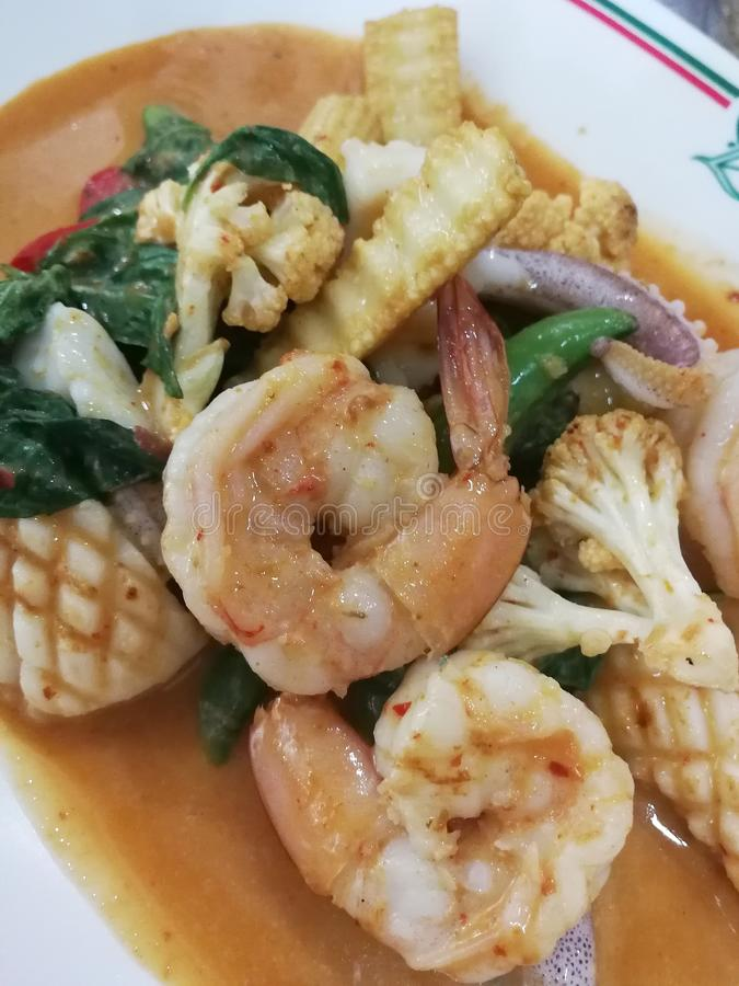 Fried prawns and squid in red curry sauce and coconut milk. / Thai food stock image