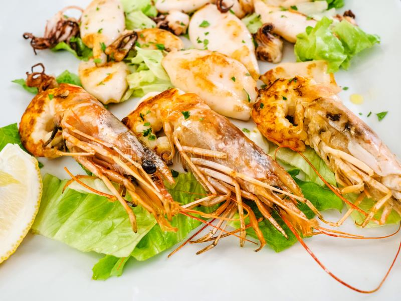 fried prawns and squids close up on white plate royalty free stock photography