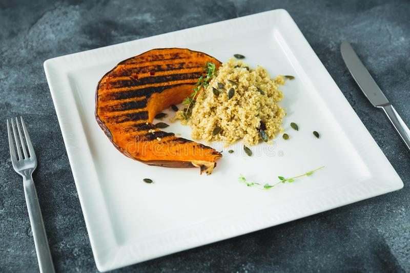 Fried pumpkin with sprouted millet and pumpkin grains on the dark table. Thanksgiving day food. Fried pumpkin with sprouted millet and pumpkin grains on the dark stock photos