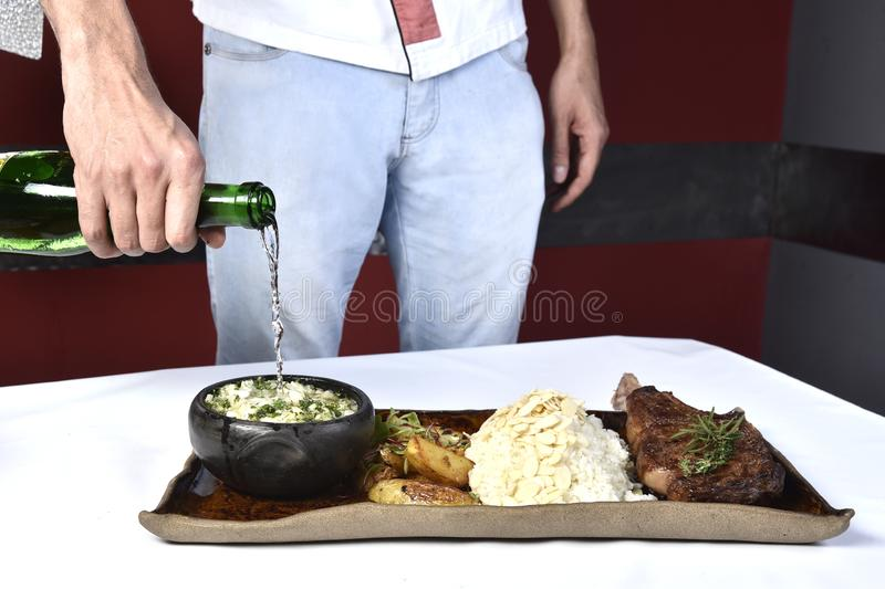 Fried ribs with rosemary, potatoes rustic, onion, sauce on wooden round Board. Dark background. Place for text, copyspace stock photography