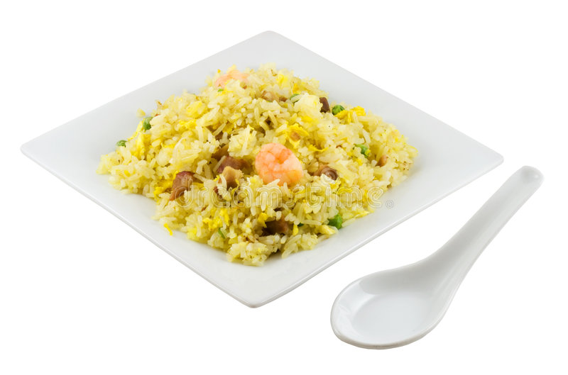 Fried Rice. A plate of fried rice and spoon isolated in solid white background royalty free stock image