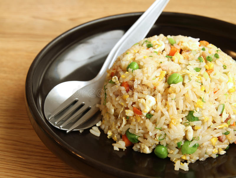 Fried rice. In black dish with spoon and fork stock photo
