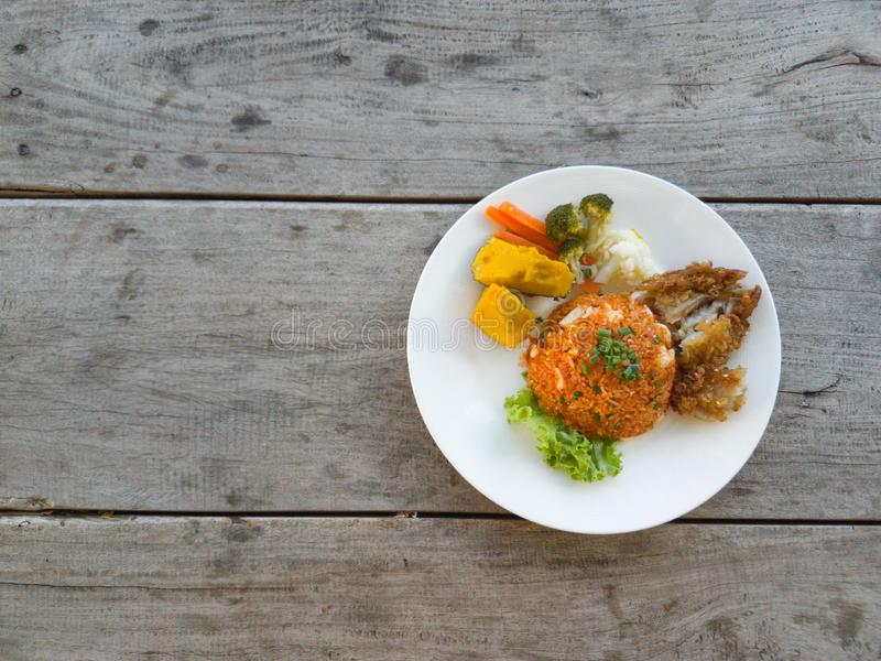 Fried rice, fried chicken  vegetables on a wooden table royalty free stock photography