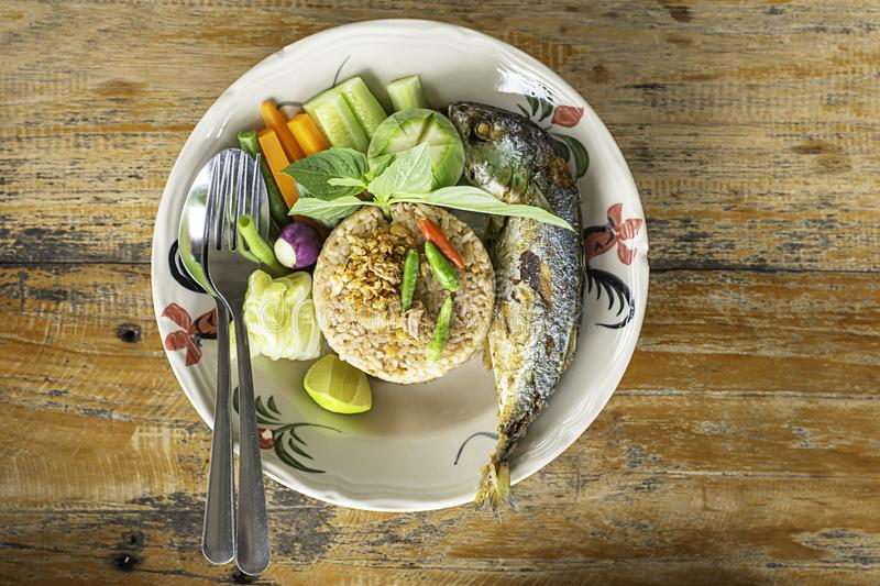 Fried rice with chili spicy with fish and vegetables in white plate on wooden table royalty free stock photo