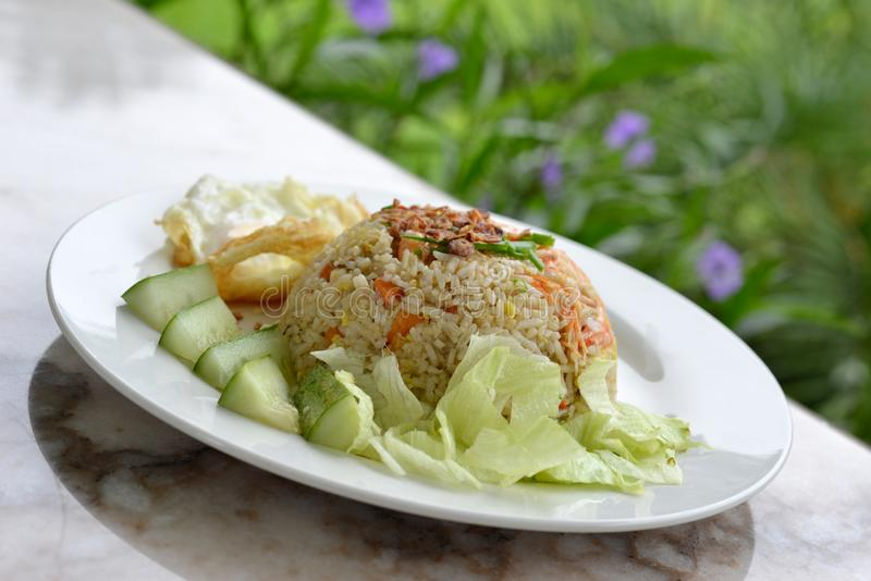 Fried Rice. Is a dish of cooked rice that has been stir-fried in a wok or a frying pan and is usually mixed with other ingredients such as eggs, vegetables stock photo