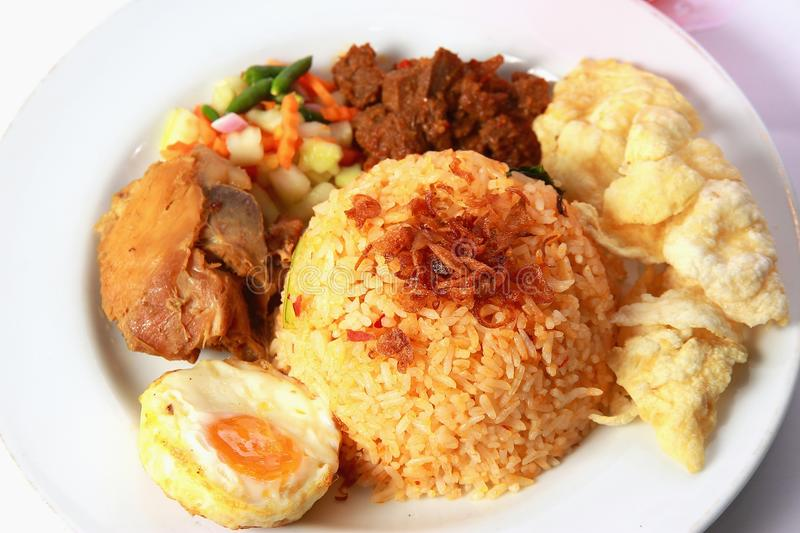 Fried Rice. Or nasi goreng, served with fried chicken, egg , satay, pickles and chips royalty free stock photos