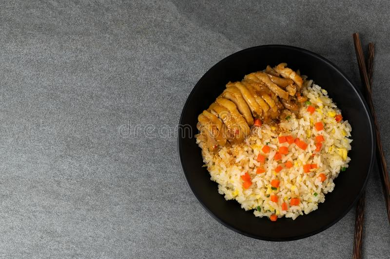 Fried rice with roast chicken and carrot in Korean style in black bowl on table royalty free stock photo