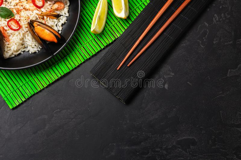 Fried rice with seafood mussels, shrimps and basil in a black plate with chopsticks on green bamboo mat and stone table stock photos