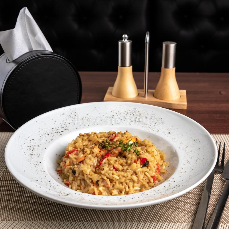 Fried Rice with Seafood, pepper shaker and napkin holder at the table of asian restaurant close up stock photos