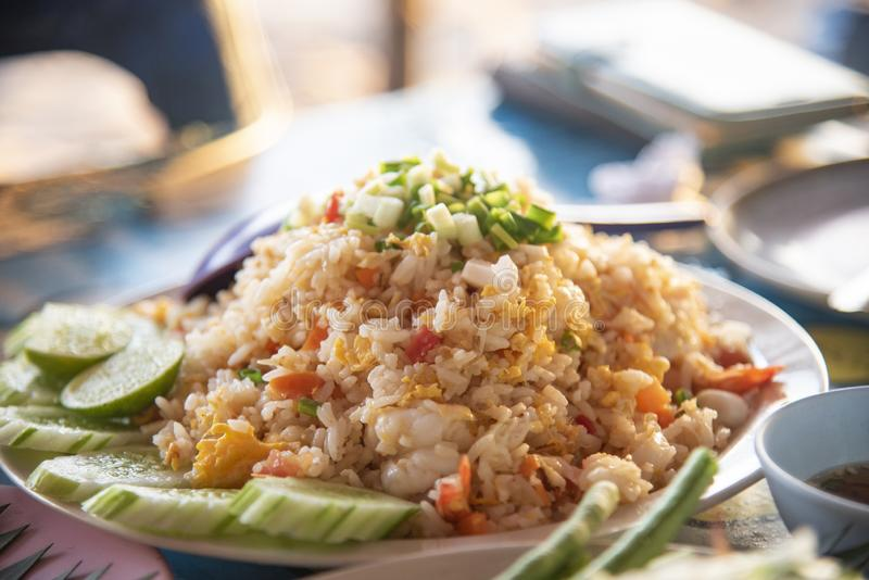 fried rice shrimp egg with seafood cucumber lime on plate on the table outdoors thai style food stock photography