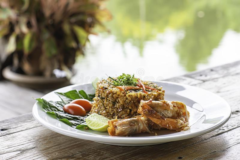 Fried rice with Shrimp on wooden table , spicy food Thai style Background rivers and trees royalty free stock image