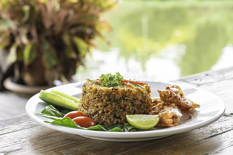 Fried rice with Shrimp on wooden table , spicy food Thai style Background rivers and trees royalty free stock photo