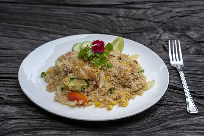 Fried rice with shrimps and vegetables in a white dish on an old wooden table, close up . Thai food , Thai cuisine. Fried rice with seafood in the restaurant stock photos