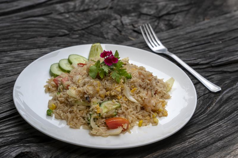 Fried rice with shrimps and vegetables in a white dish on an old wooden table, close up . Thai food , Thai cuisine. Fried rice with seafood in the restaurant royalty free stock photo