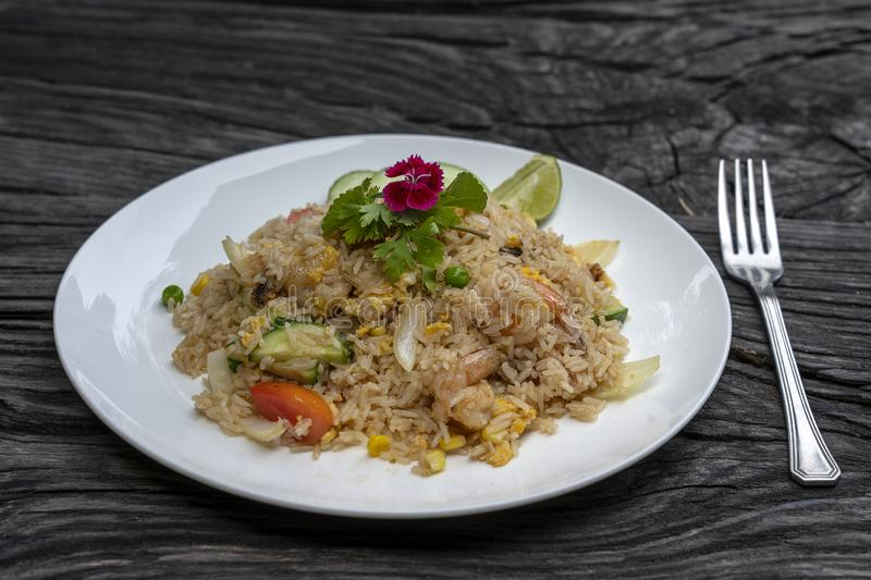 Fried rice with shrimps and vegetables in a white dish on an old wooden table, close up . Thai food , Thai cuisine. Fried rice with seafood in the restaurant royalty free stock photography