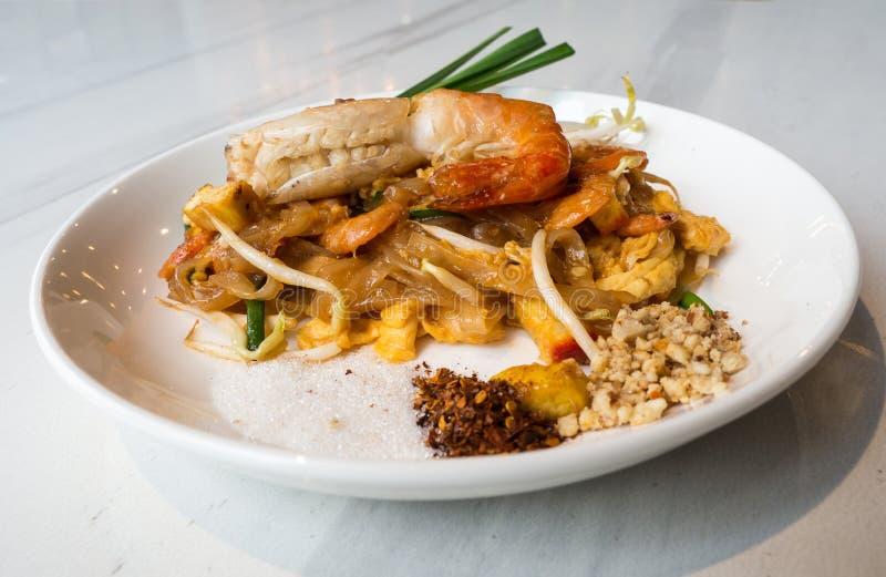 Fried Rice Sticks con el CÉSPED TAILANDÉS del COJÍN GOONG del camarón puso una placa blanca y colocado en una tabla de mármol bla imagenes de archivo