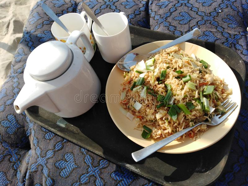 Fried rice and tea beach food Indian cuisine. Fried rice with eggs and onion on plate and tea on beach local food, Goa, India stock image