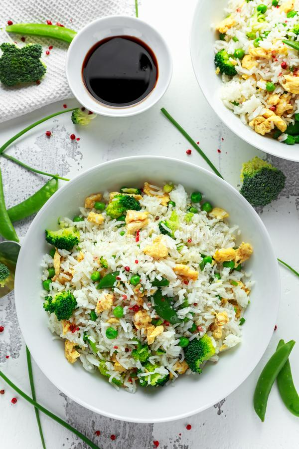 Fried rice with vegetables, broccoli, peas and eggs in a white bowl. soy sauce. healthy food.  stock image