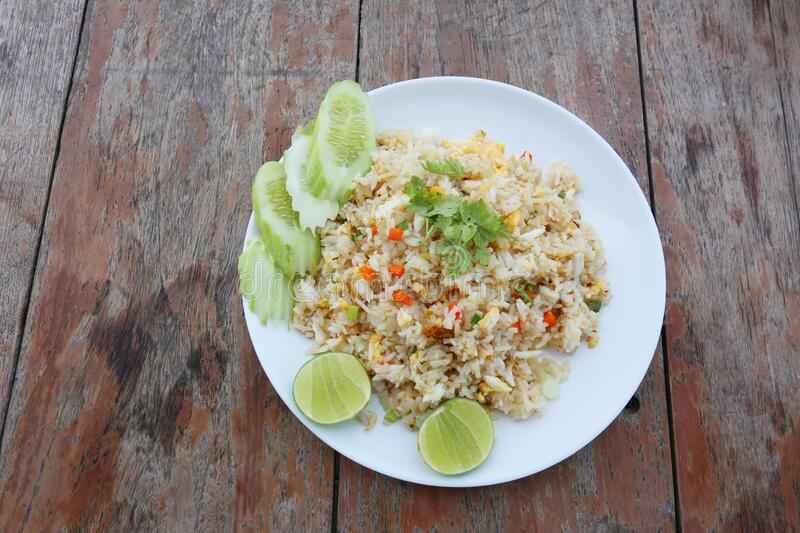 Fried rice in a white plate on an old brown wooden table stock photography