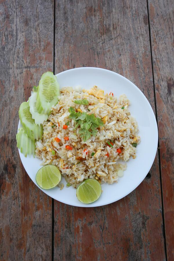 Fried rice in a white plate on an old brown wooden table stock photos