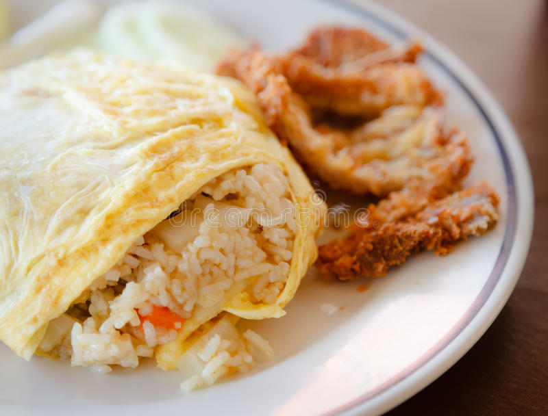 Fried rice wrapped by omelet on the white dish royalty free stock photos