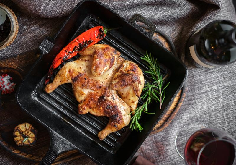 Fried roast chicken in a frying pan on a wooden Board royalty free stock images