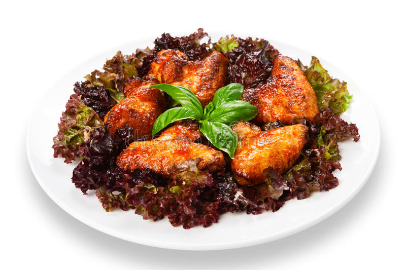 Fried roasted chicken wings on lettuce royalty free stock photo