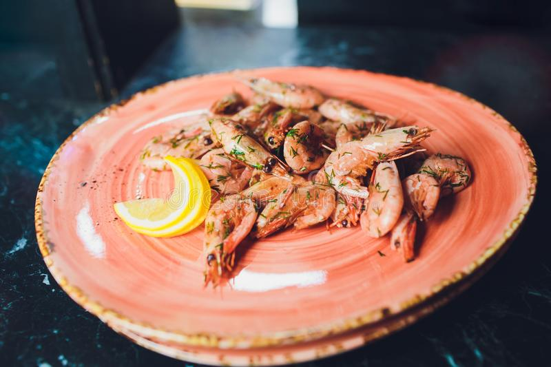 Fried roasted shrimps in plate with lemon greens parsley garlic. royalty free stock image