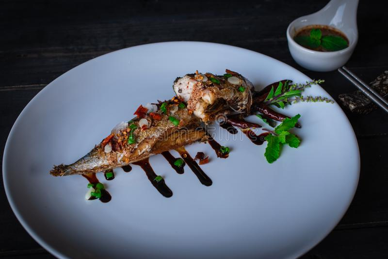 Fried Saba fish with Sauce on white plate and decoration by vegetable and sauce plated on the wood table, there are sauce in spoon. Ceramic and chopstick placed royalty free stock photo