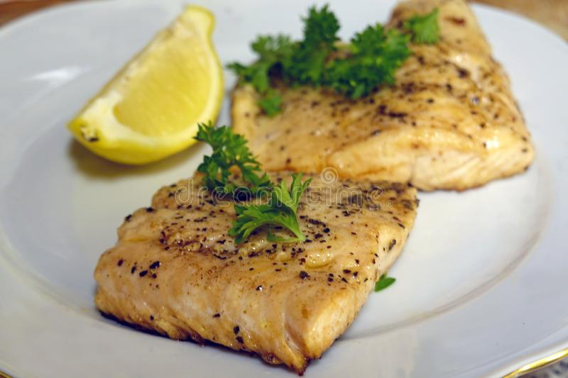 Fried salmon or trout fish fillets with dill and slice of lemon royalty free stock photo