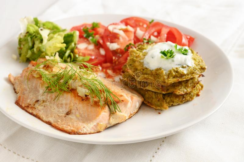 Fried salmon with vegetable pancakes and tomato salad, healthy low carb diet food, white plate on white tablecloth. Selected focus, narrow depth of field royalty free stock photo